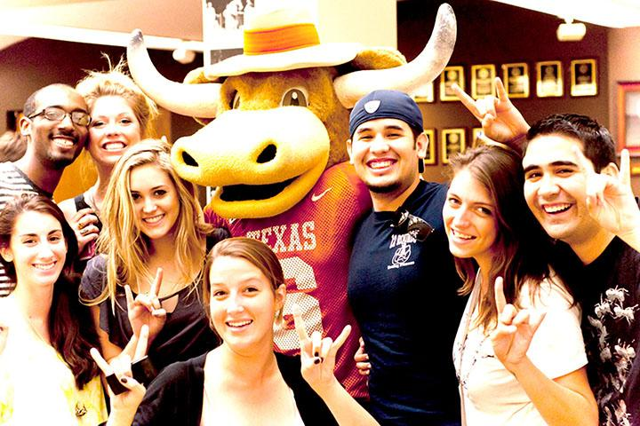 students standing with Hook Em, the UT mascot