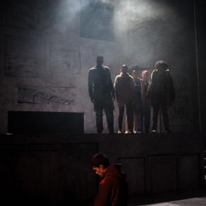 Anonymous production of actor on his knees with actors in background surrounded by haze