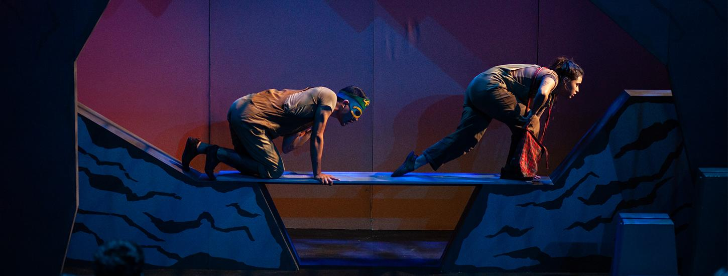 a girl and a boy with a mask on climb across a thin wooden bridge on stage