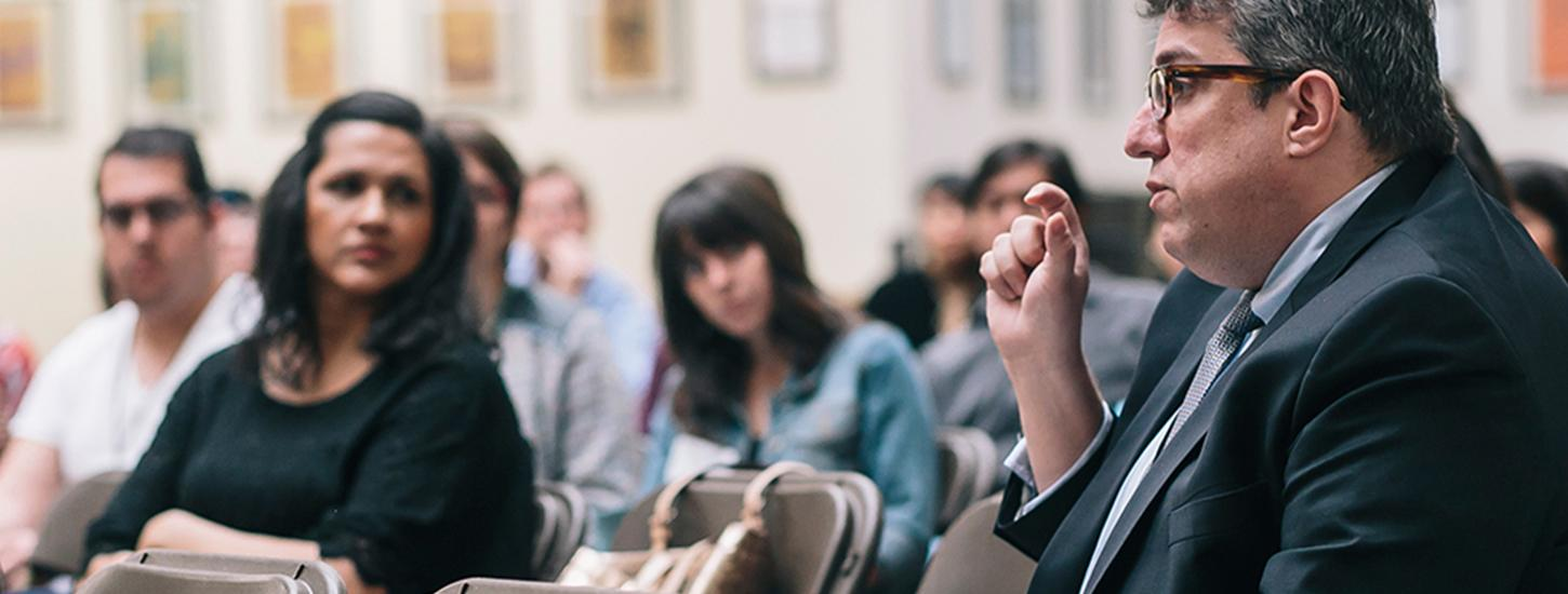 man talking to room of students