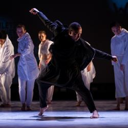 man dancing with ensemble in the background