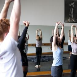 instructor and students with arms stretched overhead