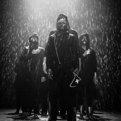 black and white image of dancers all in black under rain lighting