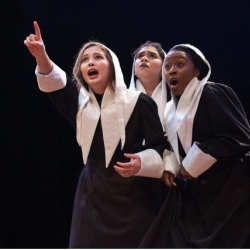Three women pointing to something out of frame in The Crucible