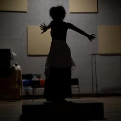 silhouette of a woman with curly hair posing with her arms stretched behind her