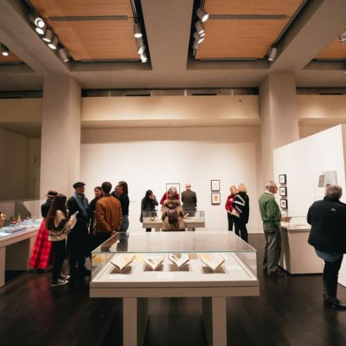multiple visitors walk around an exhibit in the Harry Ransom Center