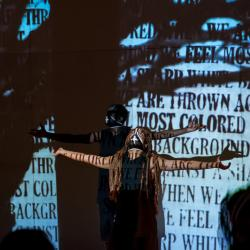woman and man in all black with black masks on look up with outstretched arms, covered with projections of words and the silhouette of a tree