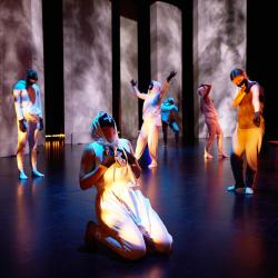 dance ensemble members wearing white hoodies and black masks pose, one on their knees, one with their arms in the air, two looking down.