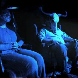 two men sitting in chairs one with skeleton on head