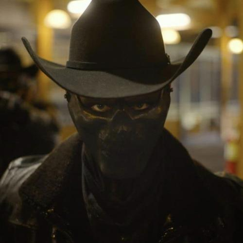 man wearing all black with a full-face mask and a cowboy hat