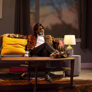 actor in a tiger striped suit coat and mask sits on a couch